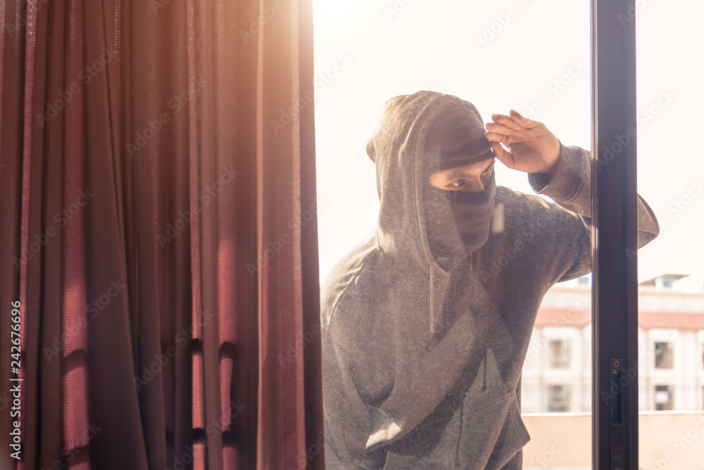 Fototapeta Burglar wearing black clothes and leather coat breaking in a house