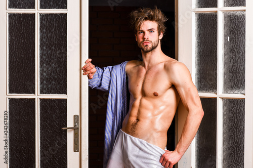 Guy shimmering sweaty skin wear bathrobe. Man athlete with fit sexy torso. Sexy lover concept. Sexy attractive macho tousled hair coming out through bedroom door. Bachelor sexy body chest and belly