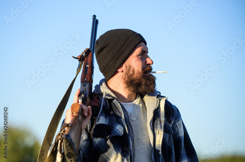 Valokuva  Man brutal bearded guy gamekeeper blue sky background