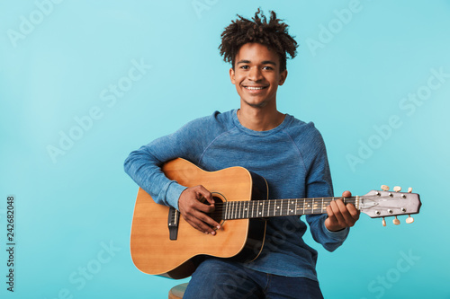 Handsome young african man playing a guitar - 242682048
