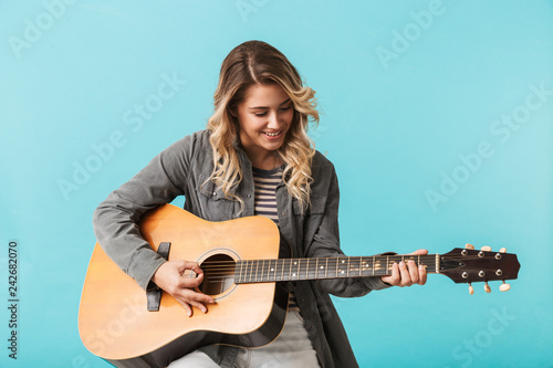 Leinwand Poster Smiling young girl playing a guitar while sitting isolated
