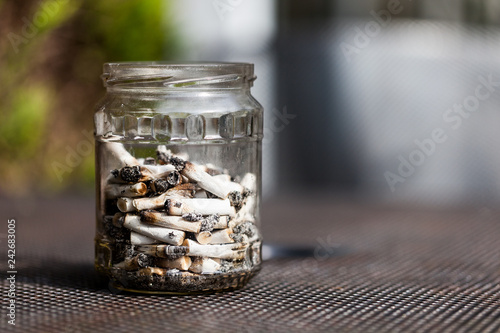 Fényképezés  Jar full with smoked cigarette filters