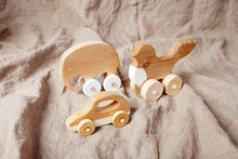 Cute Wooden Handmade Toys For Kids On Natural Linen Background. Handcrafted Toys