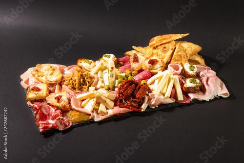 Staande foto Voorgerecht Antipasto italiano, salumi, formaggio e verdure sott'olio su sfondo scuro