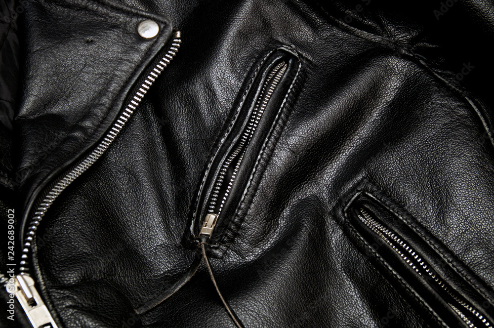 Fototapeta Detail of classic old black leather police style motorcycle jacket focusing on zippers and pockets.