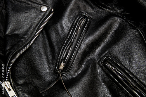Detail of classic old black leather police style motorcycle jacket focusing on zippers and pockets.