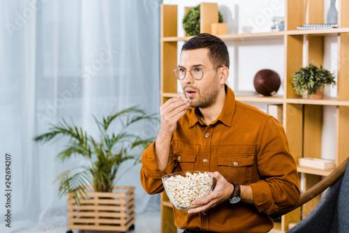 Fotografija  surprised man in glasses eating popcorn while watching movie