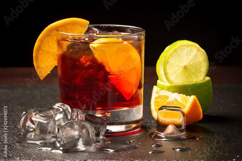 Foto op Aluminium Cocktail Cocktail rosso con ghiaccio e fette di limone in primo piano
