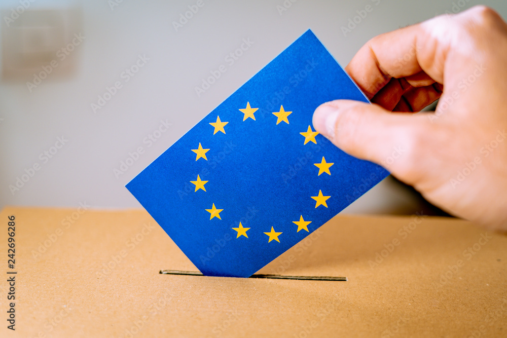 Fototapety, obrazy: Election in European Union - voting at the ballot box. A hand putting an EU flag vote in the ballot box.