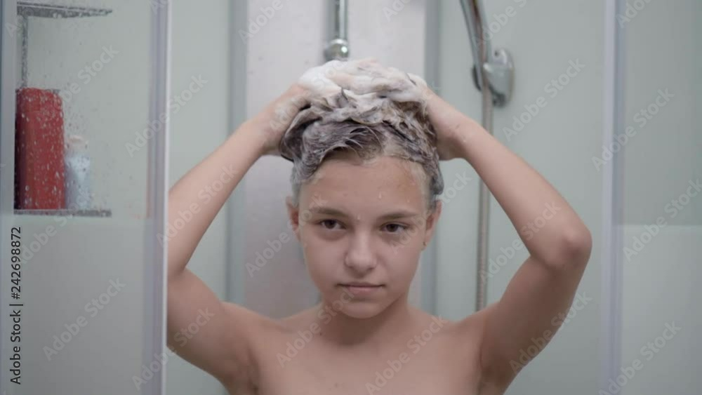 Vidéo Stock Smiling young girl bathing under a shower at home. Beautiful teen girl taking shower and washing in the bathroom. Happy child washing head, face and body with water. | Adobe Stock