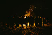 Silhouettes Of People Standing  Around Large Bonfire With Sparks Flying Around