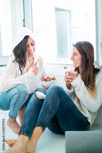 Fotografía  Two women eating fruit and drinking tea at home