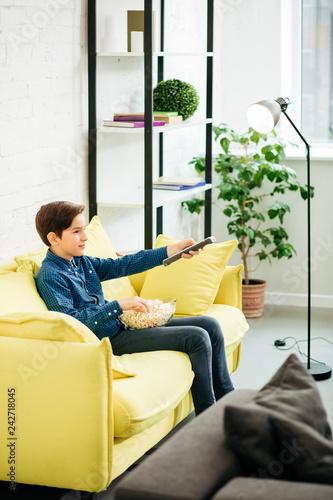 Fotografie, Obraz  Calm boy using remote control and holding bowl of popcorn