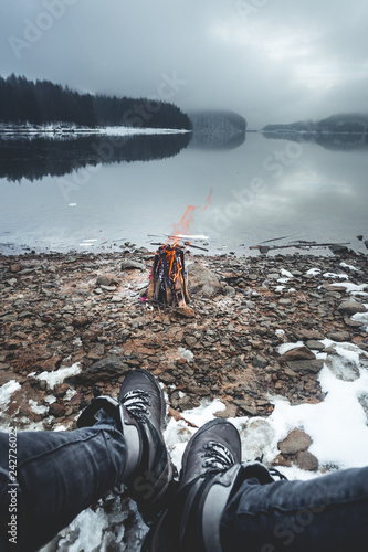 Fotografie, Obraz  Close up view of fashion male legs wearing hiking boots sitting around a campfir