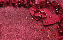 Red Background With Two Rings And A Heart, Near Small Glass Hearts And Beads With A Ribbon