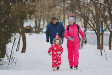 Happy Family Woman, Man And Little Girl In Warm Clothes Running, Walking In Snowy Park Or Forest Outdoors. Winter Fun, Leisure On Holidays. Love Childhood Relationship Family People Lifestyle Concept.