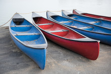 Red And Blue Rowing Boats On The Side Of A Boating Pool On An Overcast Pale Day. Exercise Boating And Rowing.