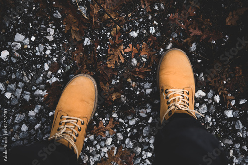 Flat Lay Of Feet Of Traveler In Old Hiking Yellow Boots