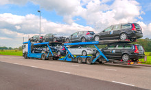 AMSTERDAM, HOLLAND-SEPTEMBER 2014. Truck Trailer Carrying Several Cars On A Highway.