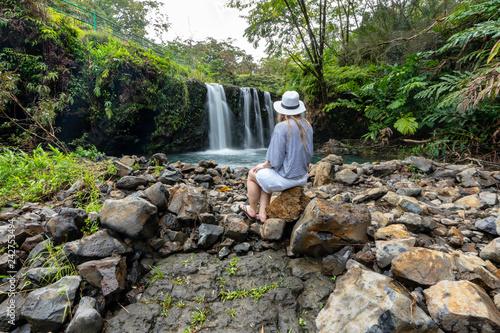 Plakat Kobieta siedząca przy wodospadzie