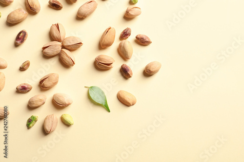 Composition with organic pistachio nuts on color background, flat lay. Space for text