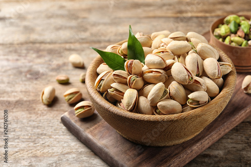 Organic pistachio nuts in bowl on wooden table. Space for text