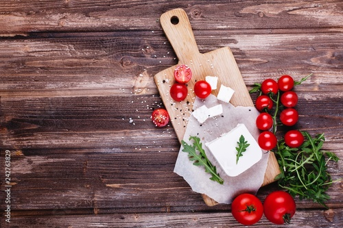 Fresh and healthy food. Delicious Italian dinner. Fresh cheese served on wooden board with arugula and cherry tomatoes on rustic wooden table