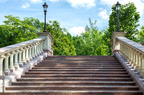 Fotografía  stone staircase with balustrade and marble steps bottom-up view in the background iron lights in retro style against the sky and green trees