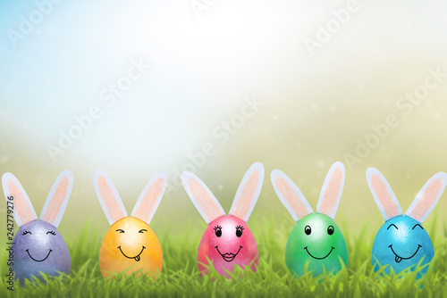 Fotografia  A row of Easter eggs with smiles in fresh green grass. A banner