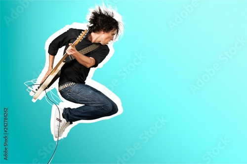 Male Guitarist playing music on grey wall background Fototapet