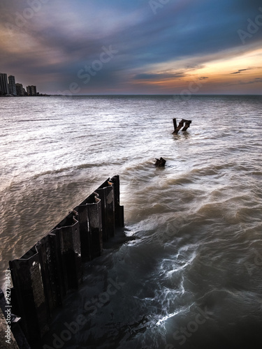 Fotografie, Obraz  A dramatic sunset photo with corrugated weathered steel piles or pilings sticking out of the choppy water and waves of Lake Michigan in Chicago