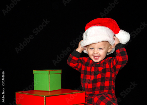 Fotografie, Obraz  Close up portrait of one one year old baby boy wearing a Santa hat playing with red and green gift boxes, both hands on hat pulling onto head big smile with baby teeth showing
