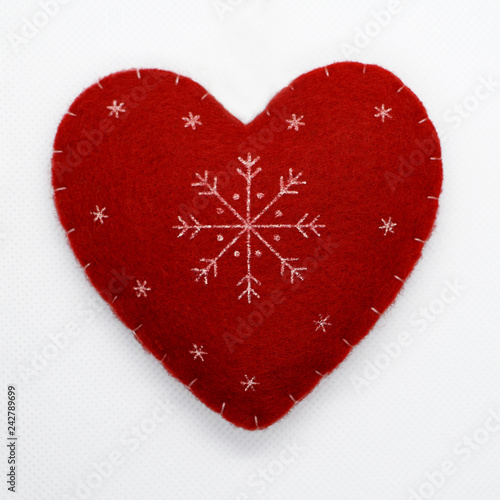 Fotografia  Handmade docorative red plush heart with snowflake ornaments on white background