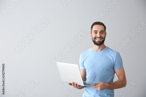 Young freelancer with laptop on light background Canvas Print