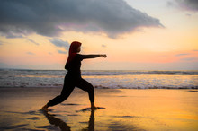Silhouette Of Young Fit Muslim Woman Covered In Islam Hijab Head Scarf Training Martial Arts Karate Punch Attack And Fitness Workout At Beautiful Beach Sunset