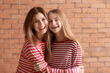 Portrait Of Happy Mother And Daughter On Brick Background