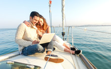 Young Couple In Love On Sail Boat Having Fun Remote Working At Laptop- Happy Luxury Lifestyle On Yacht Sailboat - Technology Concept With Influencer Travel Blogger - Warm Afternoon Color Tone Filter