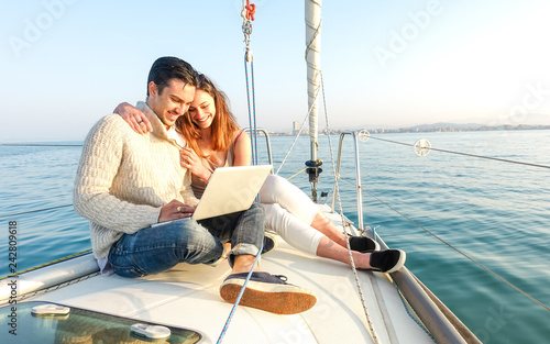 Fotografia  Young couple in love on sail boat having fun remote working at laptop- Happy lux