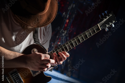 The guitarist in the hat plays solo on the electric guitar Fototapet
