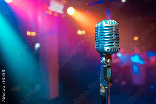 Photo  Close up retro microphone with musician playing acoustic guitar on band in night