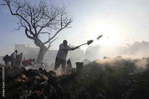 A trader uses a shovel as he attempts to recover his