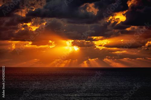 Fototapeta premium Dramatyczny zmierzch w morzu za ciemnymi ciężkimi chmurami