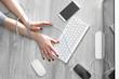 Uzależnienie od nowych technologii.  Kobieta ze związanymi dłońmi kablem pisze na klawiaturze komputera .