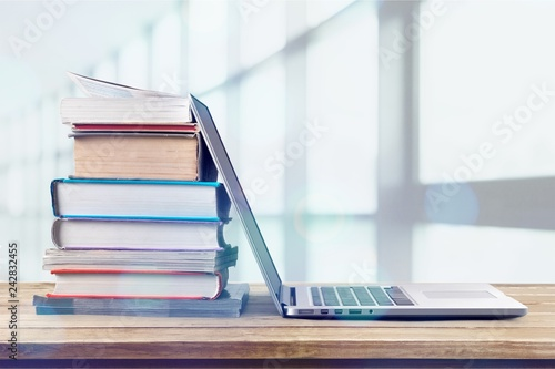 Tela Stack of books with laptop on wooden table
