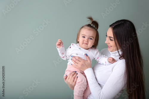 Fotobehang womenART Young woman with her cute little daughter on color background