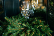 Christmas Lights Garland In Glass Bottle On Green Fir Tree Branches Over Dark Texture Background. Christmas Holiday Mood Card.