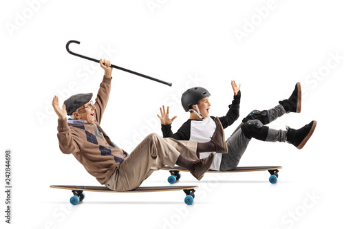 Cheerful senior with a cane sitting on a longboard and riding with his grandson