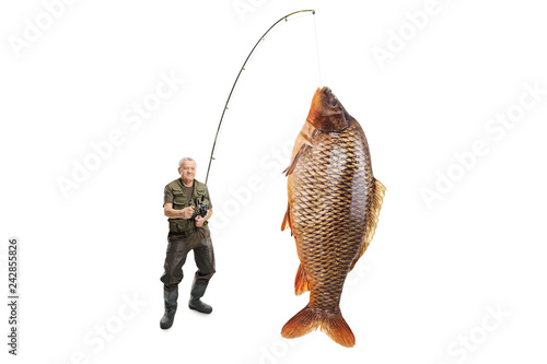 Tablou Canvas Mature fisherman with a carp fish on a fishing rod