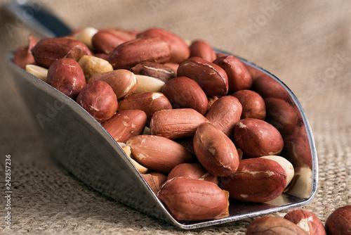 Fotografía  Metal scoop full of peeled peanuts on sackcloth