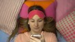 Top view of cute beautiful girl lies and uses a smartphone before falling into sleep.